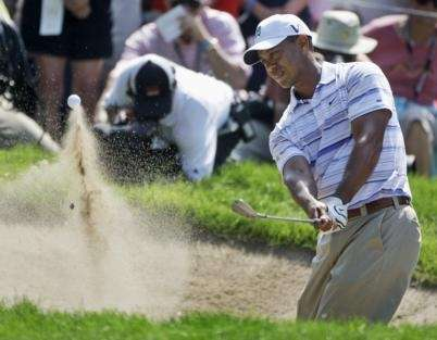 Tiger Woods hits out of a bunker on