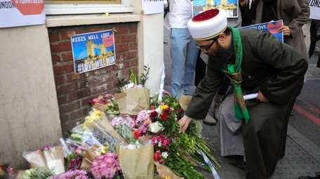 A man lays flowers on Sunday, June 4,