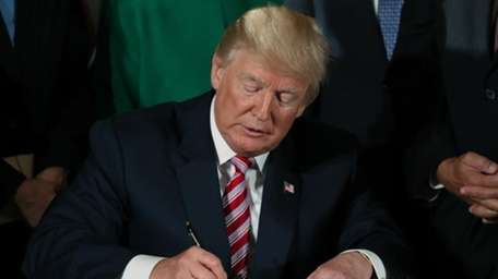 President Donald Trump signs a memo and a