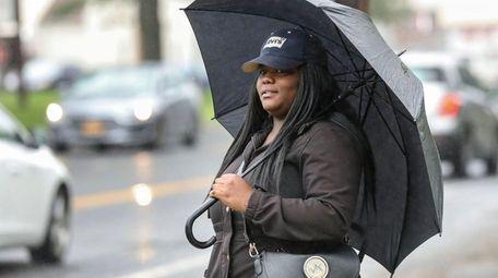 Niasia Freeman, of Mastic, waits in the rain
