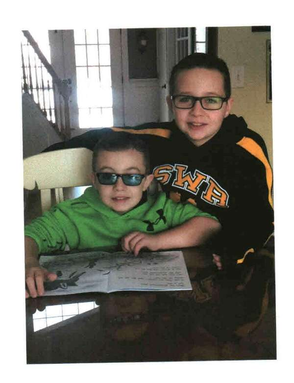 Kidsday reporter Charlie Vescovo, right, reads with his