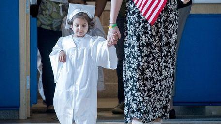 Morgan Center preschooler Isabella is escorted by Morgan