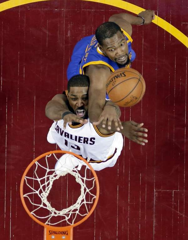 Cleveland Cavaliers' Tristan Thompson, bottom, is stopped by