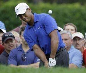 Tiger Woods watches his chip shot to the