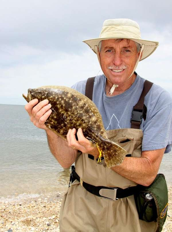 Stephen Kellner holds a fish that has a