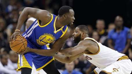Cleveland Cavaliers center Tristan Thompson, right, defends Golden