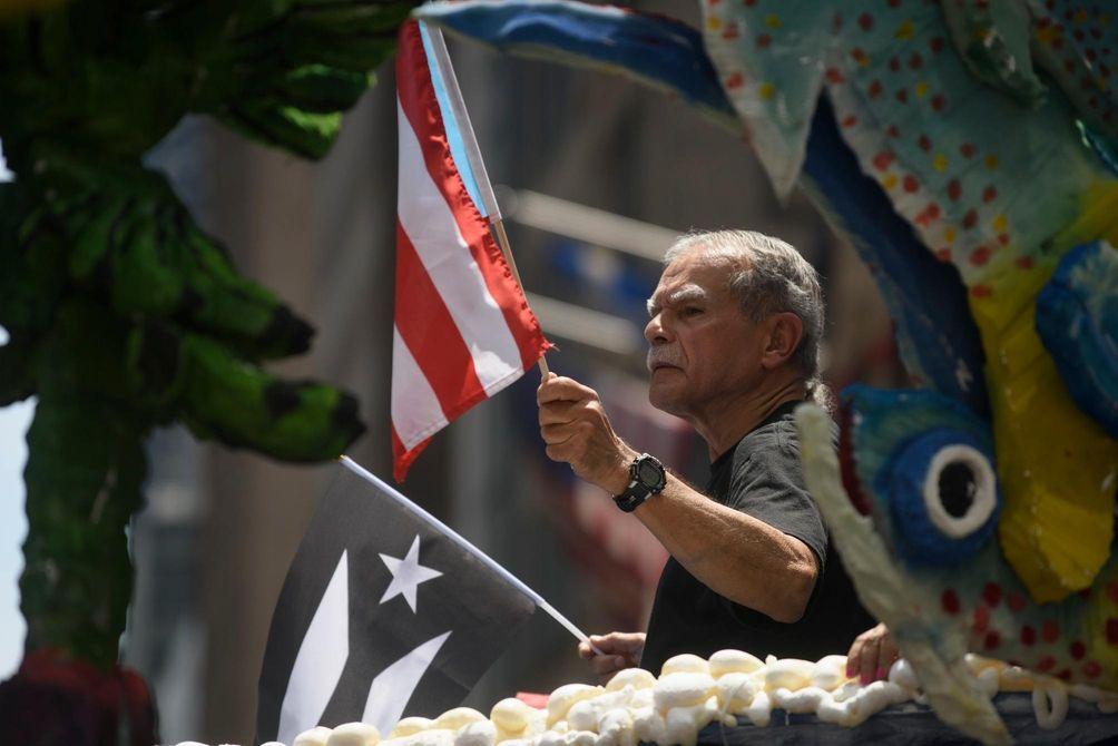 Oscar López Rivera rides on a float during