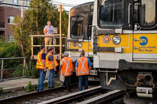 MTA employees inspect an LIRR train that struck