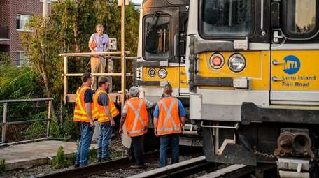 MTA employees inspect an LIRR train that struck