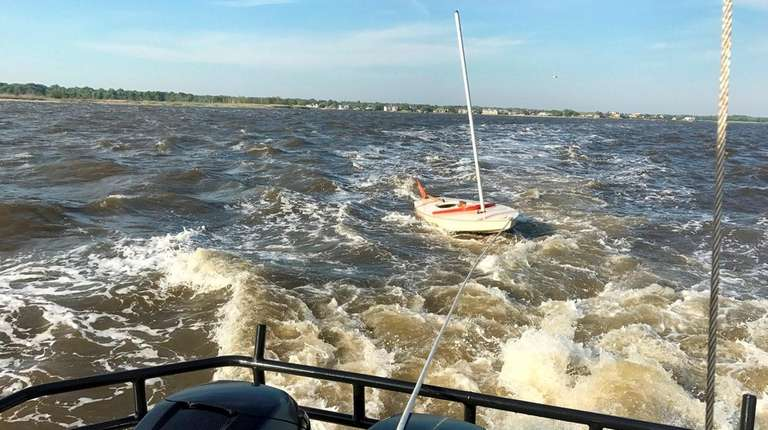 Four people were rescued after their sailboat overturned