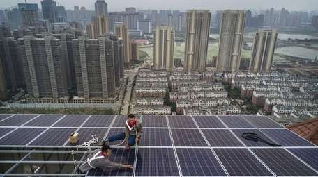 Chinese workers from Wuhan Guangsheng Photovoltaic Co. work