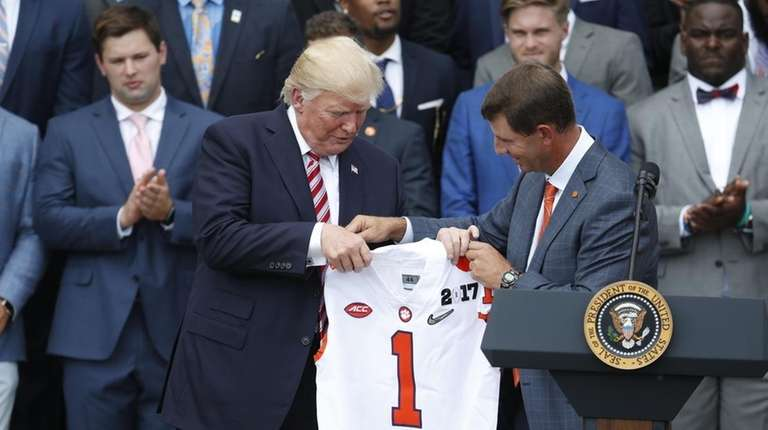 President Donald Trump holds up a jersey given