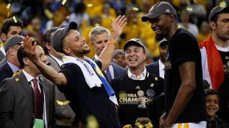 The Golden State Warriors' Stephen Curry, left, celebrates