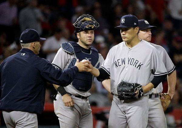 Yankees pitcher Masahiro Tanaka hands the ball to