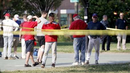 People gather near the shooting scene in Alexandria,