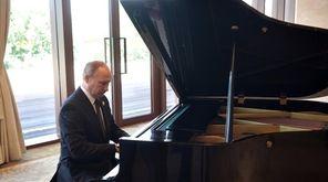 Russian President Vladimir Putin plays piano in Beijing
