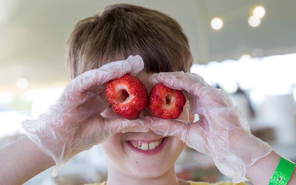 Landon Porter, 9, from Mattituck, hulls strawberries at