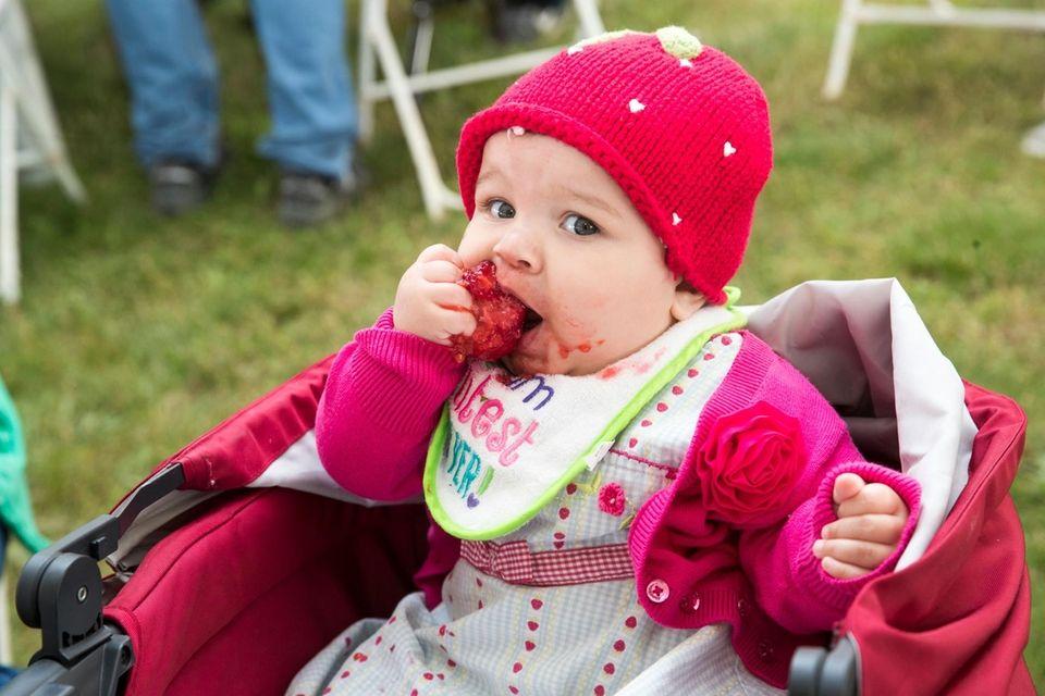 Lillee Farmer, 9 months, from Mattituck, eats strawberries