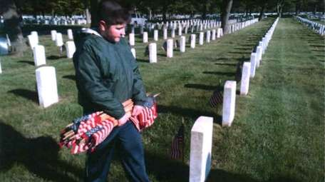 Kidsday reporter Daniel Sullivan lays flags at Long