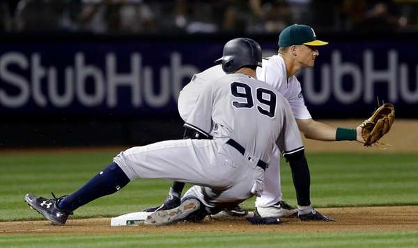 New York Yankees' Aaron Judge (99) slides safely