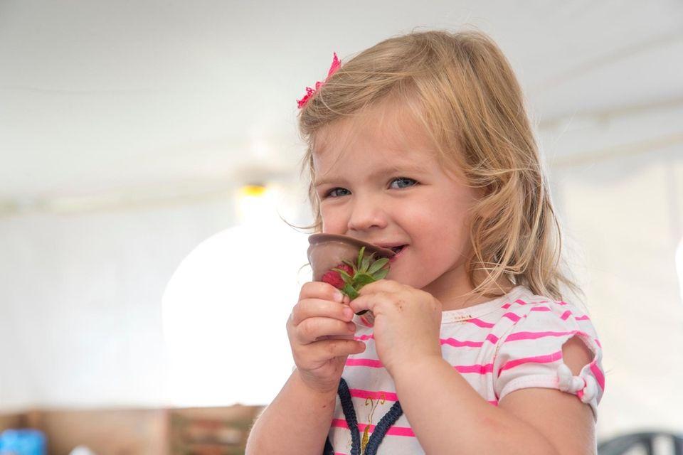 Victoria Scholtz, 2, from Mattituck, takes a bite