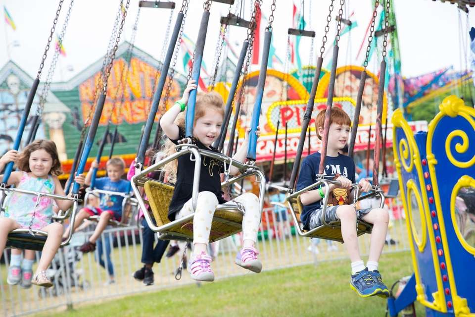 Kids enjoy amusement park rides at the 63rd