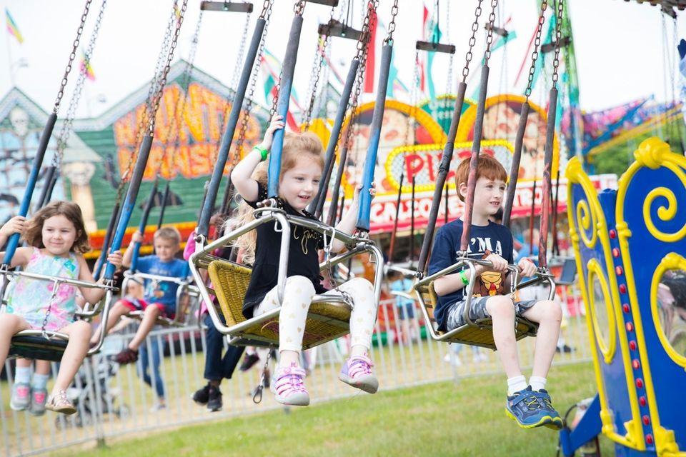 Kids enjoy amusement park rides at the 63rd