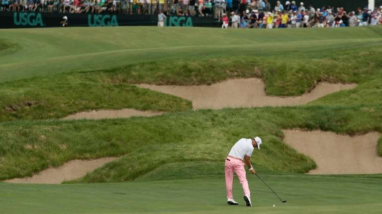 Justin Thomas hits to the 18th green during