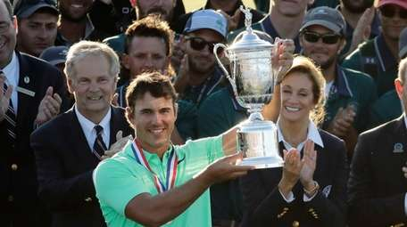 Brooks Koepka holds up the winning trophy after