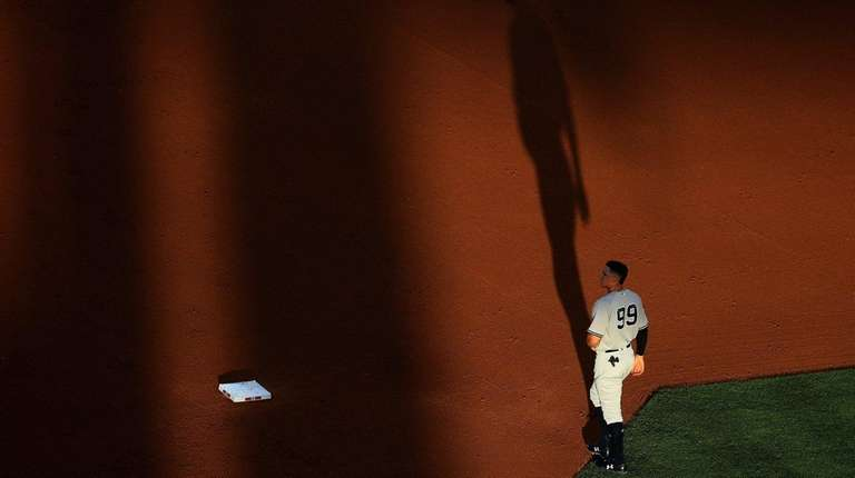 The Yankees' Aaron Judge walks to the outfield