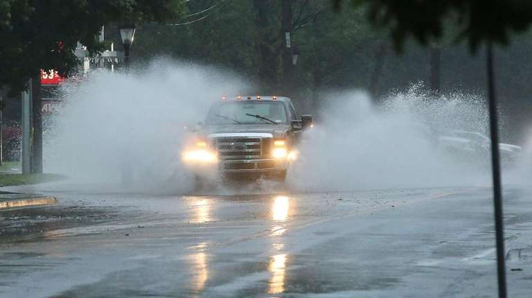 A truck passes through a soggy roadway on