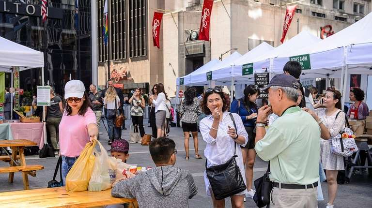 Tourists and locals shop the Greenmarket at the