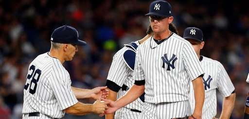 Tyler Clippard of the Yankees hands the ball