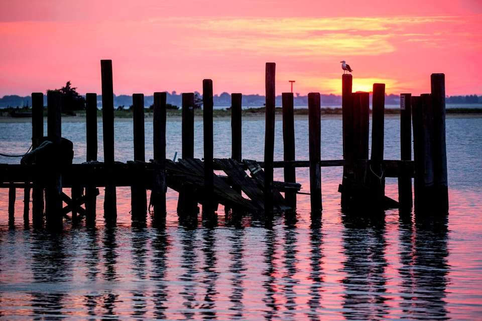 The suns rises in Greenport Harbor on Wednesday,
