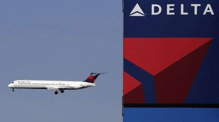 A Delta Airlines jet flies past the company's