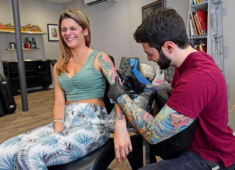Tattoo artist Joe Friedman works on Elizabeth DeMaio's
