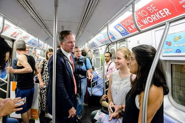 Paul Massey, left, speaks with straphangers aboard a