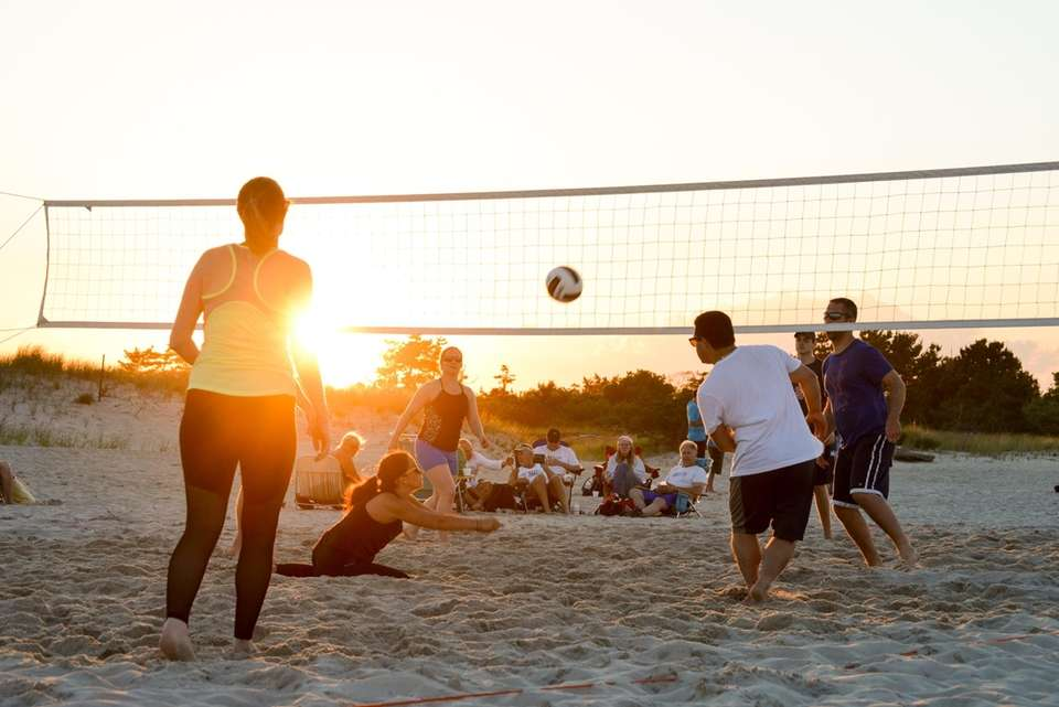 People play volleyball on the sand at Cedar