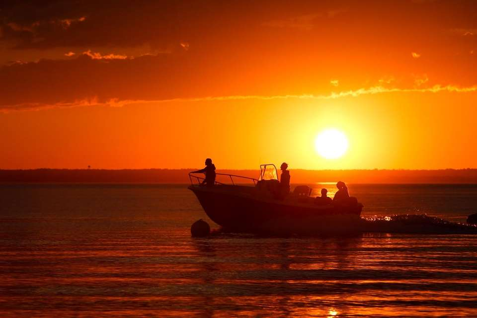Boaters cross paths with the sunset near Soundside