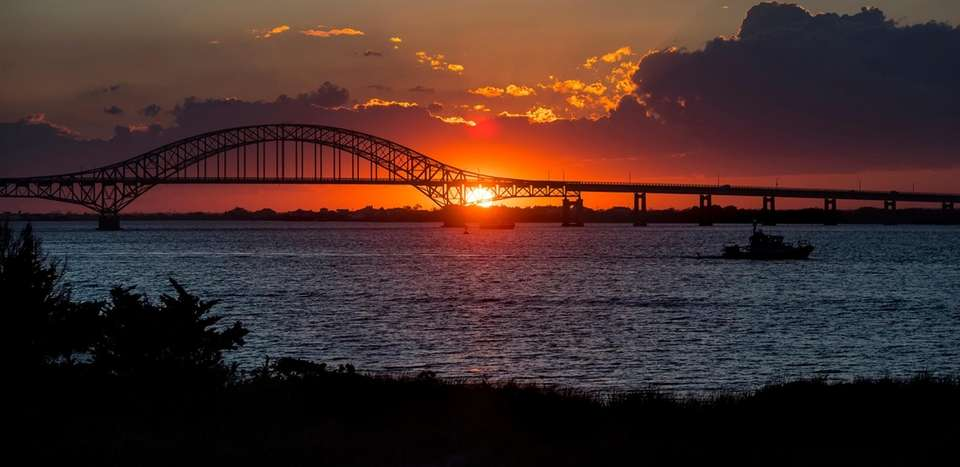 The sun sets behind Robert Moses Causeway at