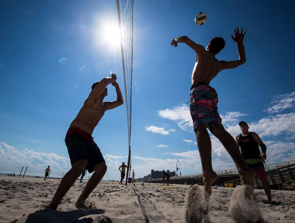 Beachgoers play volleyball in Long Beach, on Wednesday,