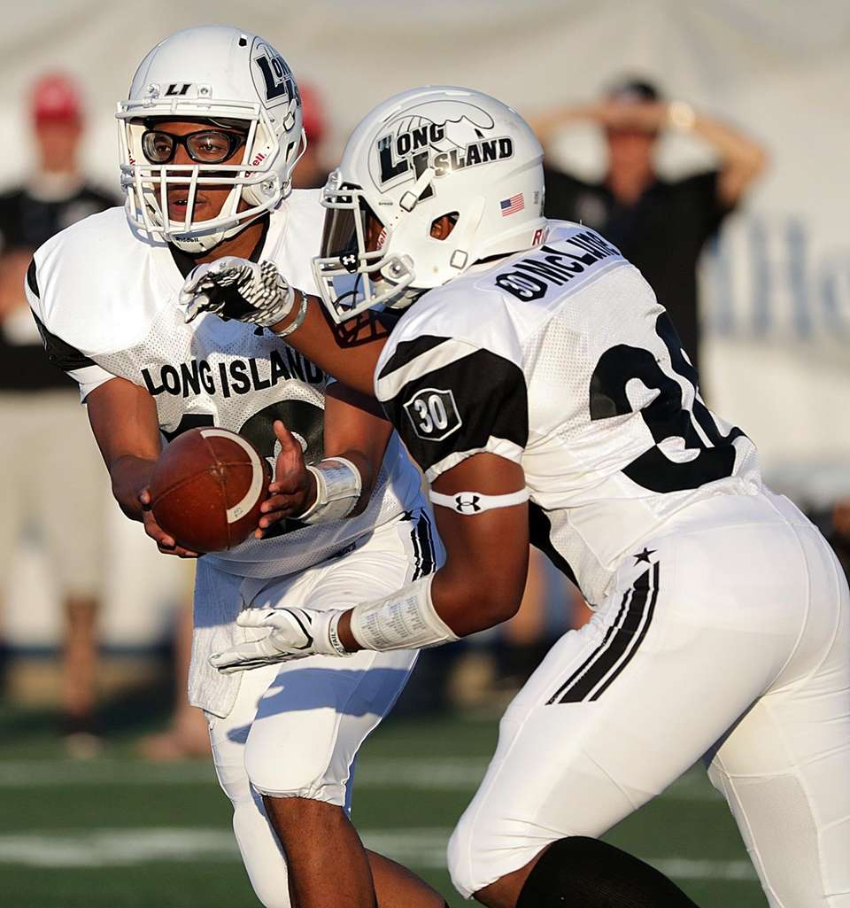 Long Island quarterback Aaron Ruthman hands off to