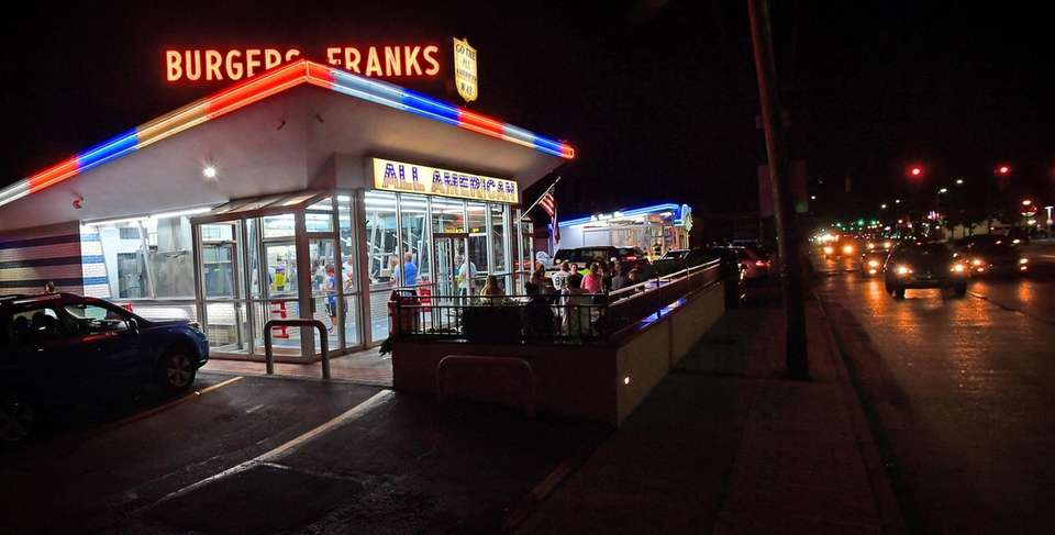 People dine under the iconic neon of Long