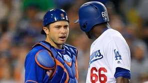 Mets catcher Travis d'Arnaud, left, says something to
