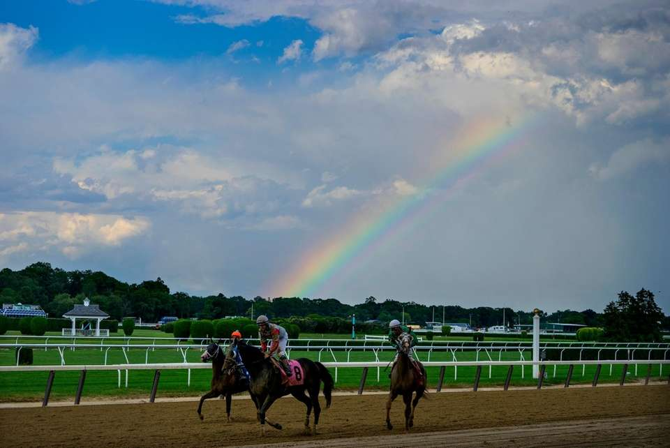 A rainbow graces the track as horses return