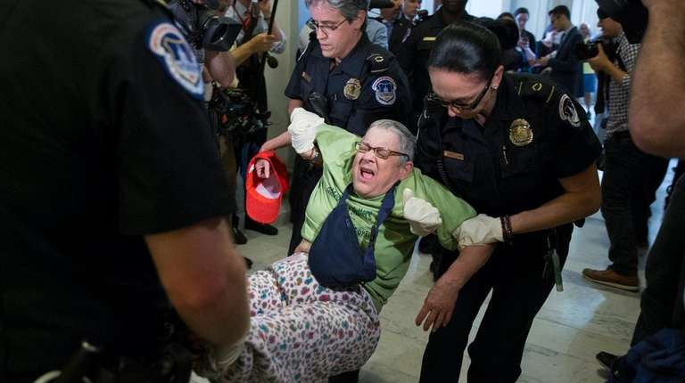 Capitol Police carry away a protester outside the