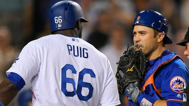Mets catcher Travis d'Arnaud, right, says something to