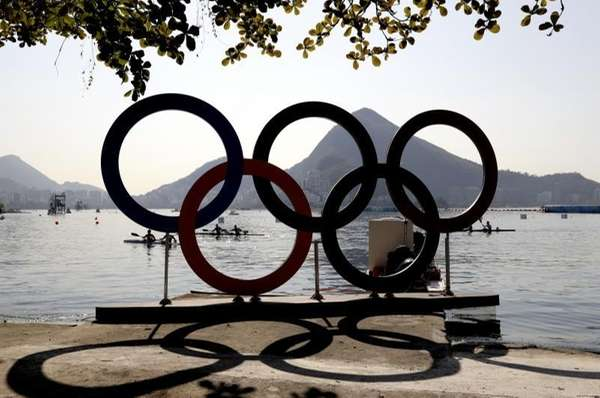 Athletes paddle to shore near the Olympic rings