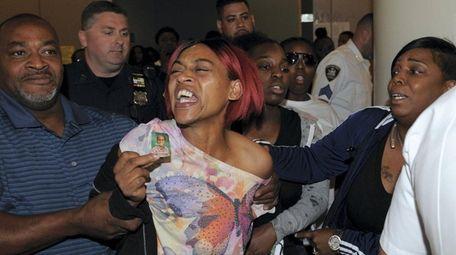 Lina Garriques, center, mother of victim Anthony Holmes-Garriques,