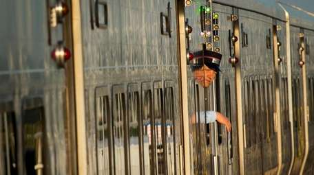 A conductor peers out of a train at